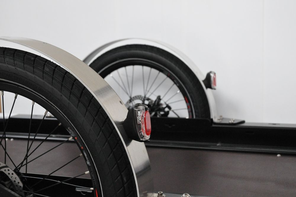 Part of the Runner bike trailer mudguards, rear lights, wheels, disc brakes and tray of the trailer