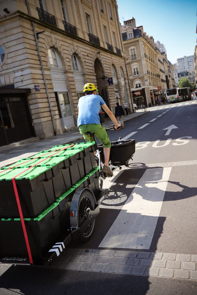 Cyclist with a blue shirt on a cargo bike towing a Runner bike trailer with 8 black boxes with a yellow lid on it riding in a bus lane